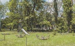 Övergiven ungelekplats i skogen Royaltyfri Bild