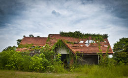 Övergivet hus i bevuxen trädgård Royaltyfri Bild