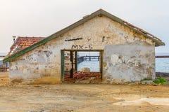 Övergivet hus vid en pir i den Argaka stranden, Cypern Royaltyfria Bilder