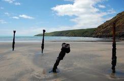 Övergivna metalrusty colimns på stranden Fotografering för Bildbyråer