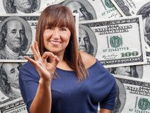 Överhopar det ok tecknet för den härliga kvinnan hundra dollar räkningar bakgrund royaltyfri bild