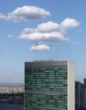 Överkant av byggnad för United Nations sekretariat med pösig vit clou Royaltyfri Bild