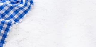 Överkant av den blåa rutiga bordduken för sikt på vitmarmortabellen royaltyfri fotografi