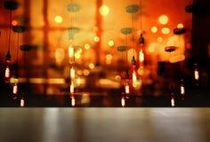 Överkant av den wood tabellen med ljus av lampkulan i bar- eller stångparti in royaltyfri foto