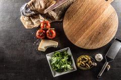 Överkant av för pizzabräde för sikt tom parme för basilika för vitlök för oliv för tomater royaltyfria bilder