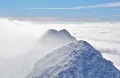 Överkant av höga berg som täckas av snö och dimma Arkivbild
