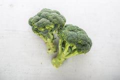 Överkant av ny broccoli för sikt på vitbetongbakgrund Fotografering för Bildbyråer