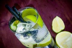 Överkant av sikten av coctailexponeringsglas med is- och limefruktskivan Arkivfoto