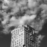 Överkant av skyskrapan som når moln Arkivfoton