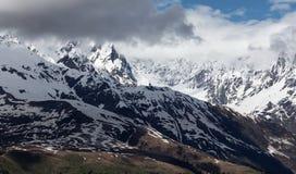 Överkant för berg för landskapfoto snöig ett soligt och dolt med moln, Mestia Royaltyfria Bilder