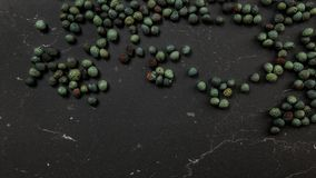 Överkant ner sikt, krydda för svartpepparpipblåsarenigrum som spills på mörkt funktionsdugligt bräde Turkiskt göra grön/den blåa  royaltyfri fotografi
