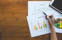 Överkant - sikt av den hållande pennan för hand med den affärsöversikts- eller för affärsplan rapporten med diagram och grafer i  Royaltyfri Fotografi