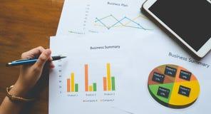Överkant - sikt av den hållande pennan för hand med den affärsöversikts- eller för affärsplan rapporten med diagram och grafer i  Royaltyfria Foton