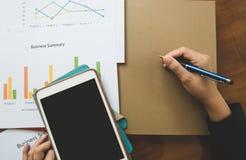 Överkant - sikt av den hållande pennan för hand med den affärsöversikts- eller för affärsplan rapporten med diagram och grafer i  Fotografering för Bildbyråer
