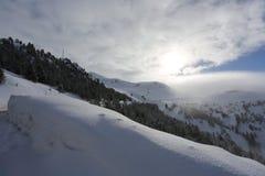 Överkanten av bergen med skogen som täckas med snö, dimma och moln på en solig frostig dag royaltyfri fotografi
