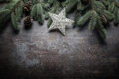 Överkanten av klirr för garneringar för siktsjulstjärnan sätter en klocka på granträdet för att sörja kottar på fri konkret bakgr royaltyfri foto