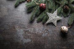 Överkanten av klirr för garneringar för siktsjulstjärnan sätter en klocka på granträdet för att sörja kottar på fri konkret bakgr royaltyfri fotografi