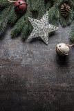 Överkanten av klirr för garneringar för siktsjulstjärnan sätter en klocka på granträdet för att sörja kottar på fri konkret bakgr arkivbild