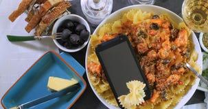 Överkanten stänger sig ner upp sikt av pasta med den nya laxen, svarta oliv och smartphonen Royaltyfria Bilder
