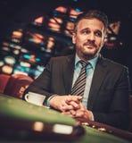 Överklassman bak dobbleritabellen i en kasino arkivbilder