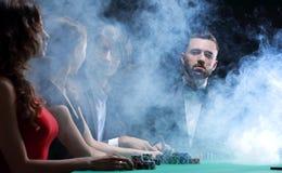 Överklassvänner som spelar i en kasino royaltyfri fotografi