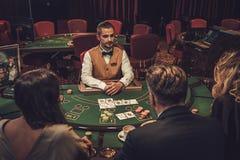 Överklassvänner som spelar i en kasino arkivfoto