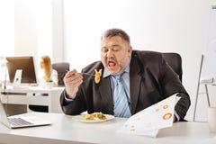 Överlastad upptagen affärsman som har lunch på arbete Fotografering för Bildbyråer