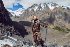 Överlevnad i det löst En man i kamouflage som vilar bland bergen Stalkeren fortlever i träna Arkivbild