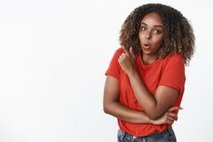 ?verraska att intressera St?ende av den roade och f?rv?nade attraktiva unga kvinnan f?r afrikansk amerikan 25s i r?d t-skjorta vi royaltyfria foton