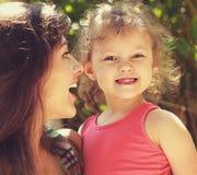 Överraskande lycklig moder som ser på rolig unge Royaltyfri Foto