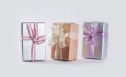 Överraskninggåvaaskar på grå bakgrund Packe för papp för fotosilver guld- med färgrika band Royaltyfri Foto