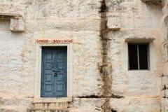 Översättning: Ett lantligt fönster och en dörr på ett ashramkomplex in arkivfoto