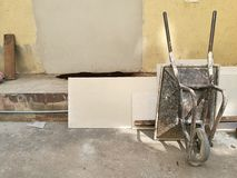 Översida för vagn för konstruktionsmetallskottkärra stående på det högra hörnet på väggen för byggnad för otvungenhet för konstru Royaltyfria Bilder