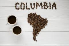 Översikt av Columbiaen som göras av grillade kaffebönor som lägger på vit trätexturerad bakgrund med två kaffekoppar Arkivfoton