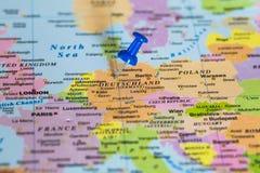 Översikt av Deutschland med en klibbad blå häftstift Arkivfoto