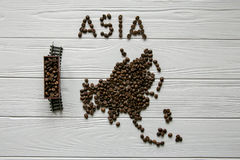 Översikt av Indliaen som göras av grillad kaffebeanMap av Asien som göras av grillade kaffebes som lägger på vit trätexturerad ba Royaltyfri Fotografi