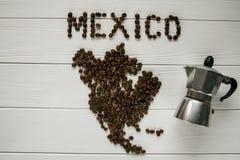 Översikt av Mexico som göras av grillade kaffebönor som lägger på vit trätexturerad bakgrund med kaffebryggaren Royaltyfri Fotografi
