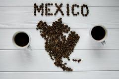Översikt av Mexico som göras av grillade kaffebönor som lägger på vit trätexturerad bakgrund med två koppar kaffe Arkivfoto