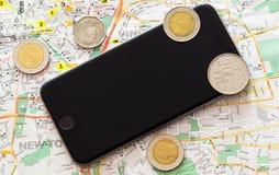 Översikt av staden, på översikten en handväska, mynt och en mobiltelefon Sommartur, semester, en fridag, en tur till Europa royaltyfria bilder