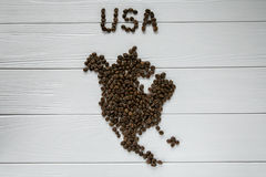 Översikt av USA som göras av grillade kaffebönor som lägger på vit trätexturerad bakgrund Fotografering för Bildbyråer