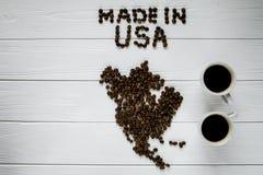 Översikt av USA som göras av grillade kaffebönor som lägger på vit trätexturerad bakgrund med två koppar kaffe Royaltyfria Bilder