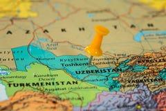 Översikt av Uzbekistan med en klibbad gul häftstift Royaltyfri Bild