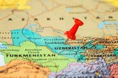 Översikt av Uzbekistan med en klibbad röd häftstift Arkivbilder