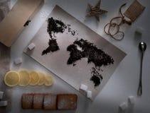 Översikt av världen som fodras med teblad Eurasia Amerika, Australien, Afrika Tappning socker anmärkning, smällare, sked överkant Arkivfoto