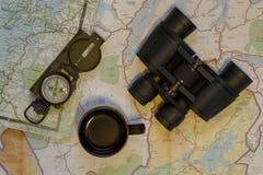 Översikter, kikare, kompass och kopp Arkivbild