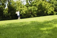 Översiktsmannen som spelar bollen, och slagträet parkerar in på grönt gräs arkivbilder