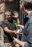 Översittare med en bruten flaska som tar pengar från offer royaltyfria foton