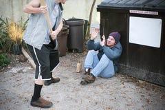 Översittaren hotar den hemlösa mannen Royaltyfri Bild