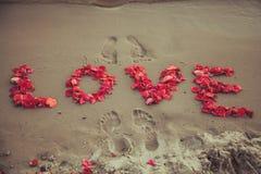 Överskriftordförälskelse i sanden av havet. Förälskelseinskrift från kronbladen av rosor. Royaltyfri Foto