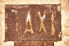 Överskrifttaxi på en rostig metallplatta royaltyfri fotografi